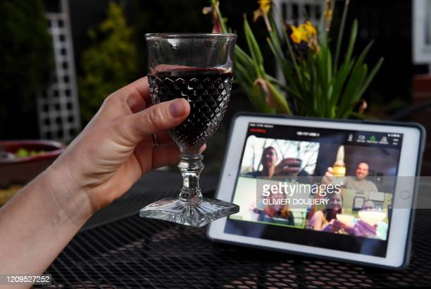 A woman lifts her glass and cheers with friends during a virtual happy hour amid the coronavirus crisis on April 8 in Arlington Virginia With bars...