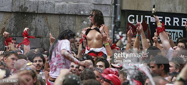 A woman lifts her top in a crowd celebrating Chupinazo during the first day of the San Fermin Running of the Bulls Fiesta on July 6 2006 in Pamplona...