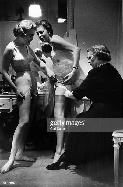 A woman lifts her tulle underskirt allowing the wardrobe assistant to attach her suspenders to her stockings Original Publication Picture Post 7899...