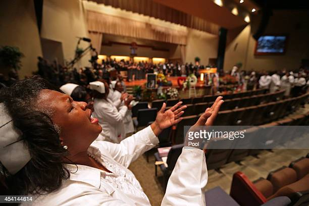 A woman lifts up her hands during the funeral of Michael Brown inside Friendly Temple Missionary Baptist Church on August 25 2014 in St Louis...