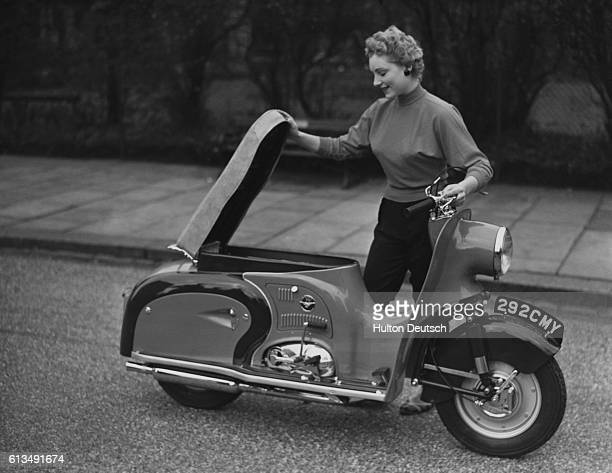 A woman lifts up the seat to give access to the petrol tank in the first British motorscooter the Dayton Albatross produced by the Dayton Cycle...