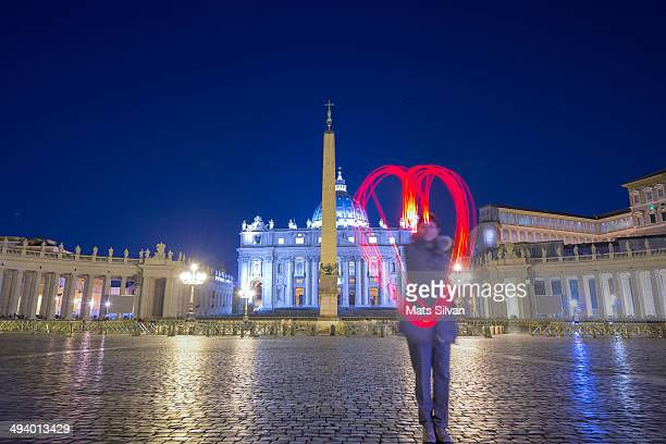 Woman light paint a heart in front of vatican City in blue hour. Rome Italy.