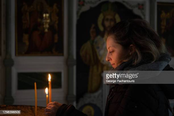 woman lighting a candle in a greek orthodox church - greek orthodox easter stock pictures, royalty-free photos & images