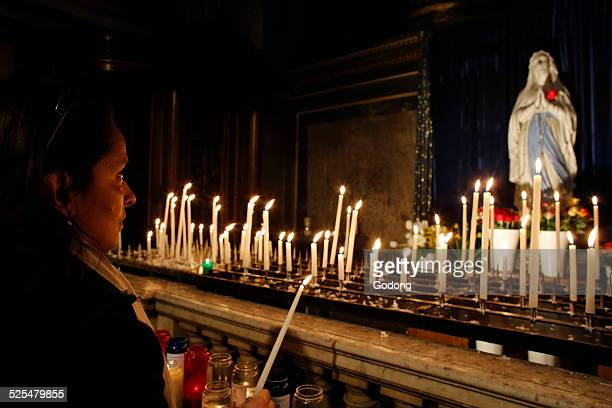 Woman lighting a candle in La Madeleine church