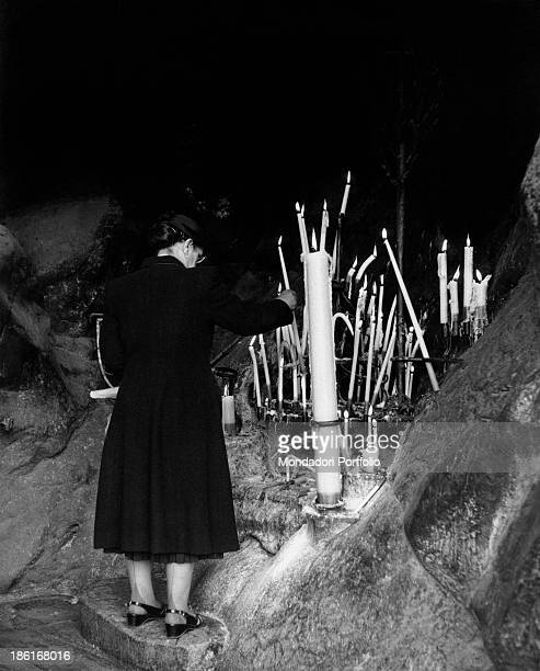 Woman lighting a candle in the Grotto of Massabielle during the centenary of the apparitions of Our Lady to Saint Bernadette Soubirous Lourdes 22nd...