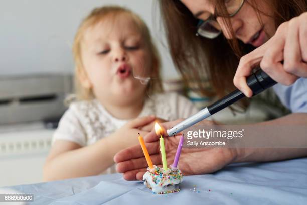 Woman lighting a candle on a cake
