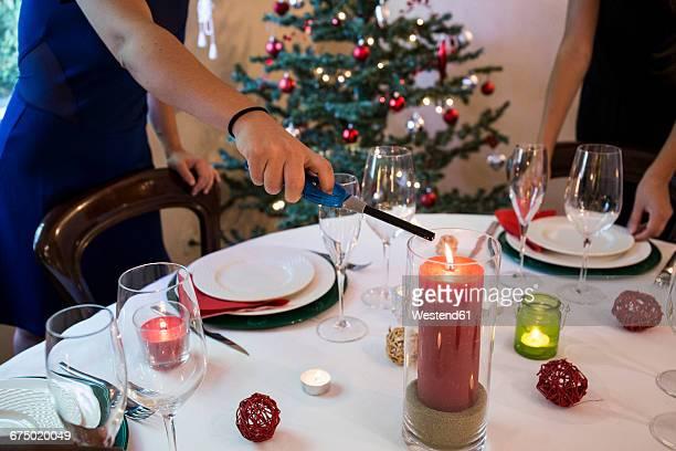 Woman lighting a candle on Christmas dinner table