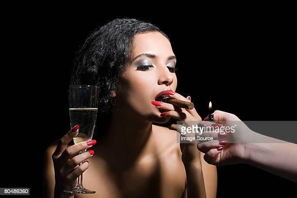 woman lighting a cigar - beautiful women smoking cigars stock photos and pictures