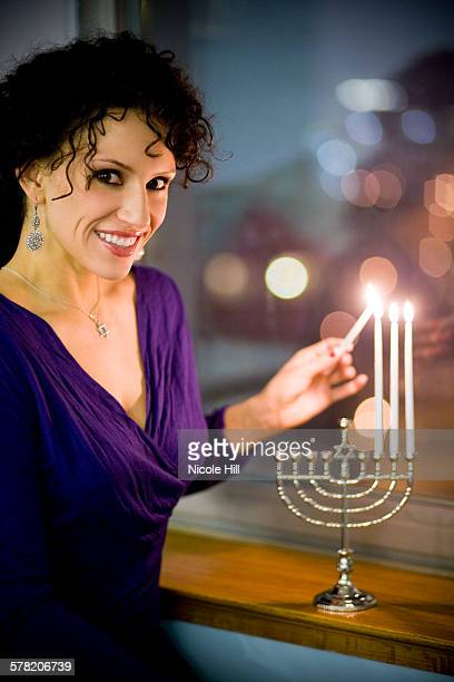 woman lighting a menorah - hannukkah stock pictures, royalty-free photos & images