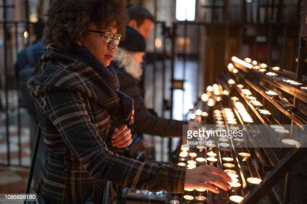 woman lighting candle in church - candle of hope stock pictures, royalty-free photos & images