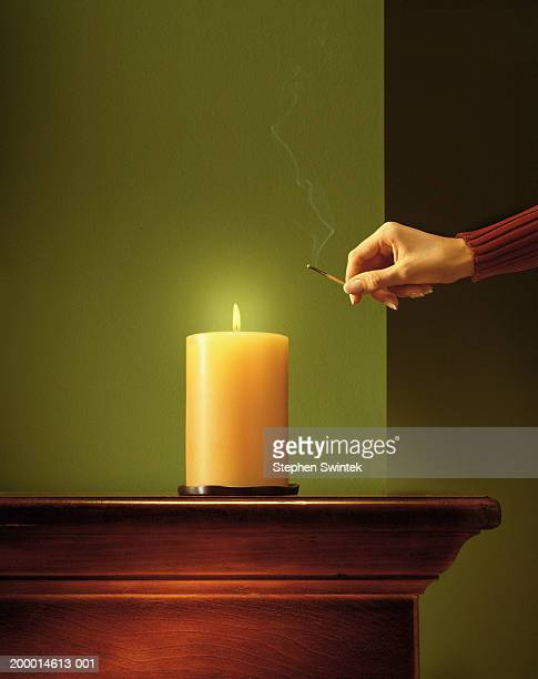 woman lighting candle with match - candle stock pictures, royalty-free photos & images