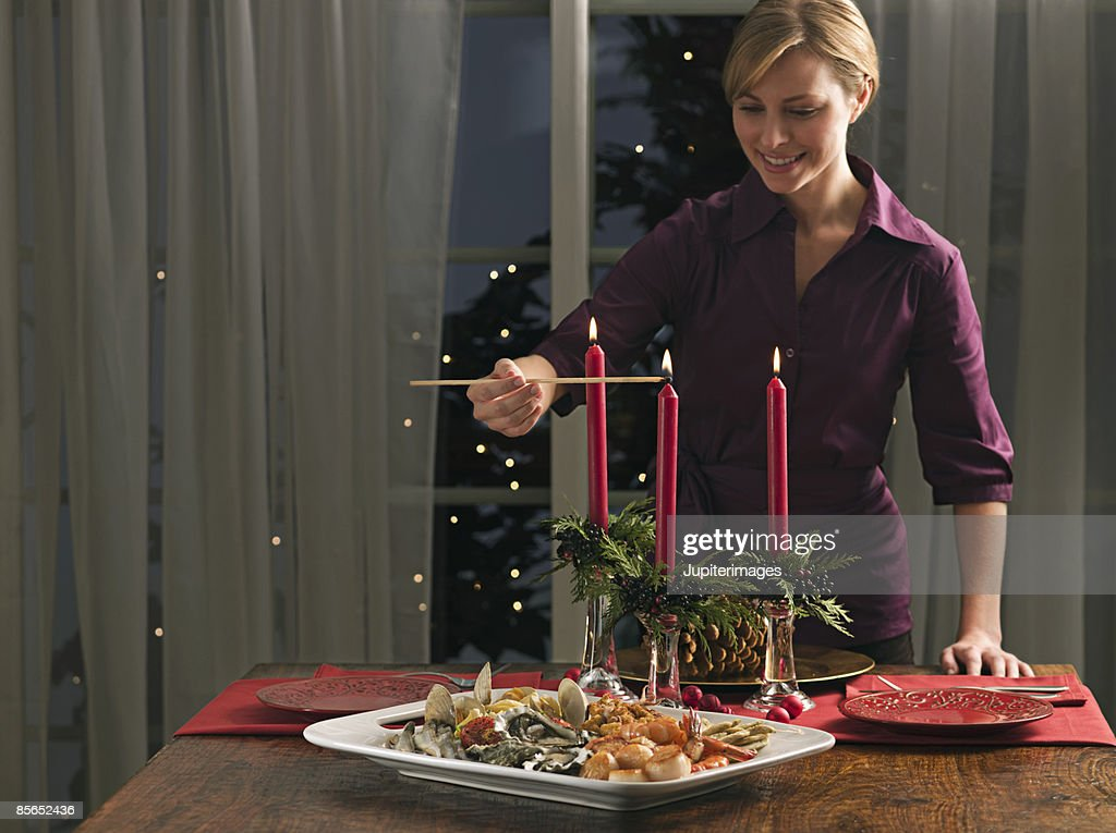 Woman lighting candles and seafood platter : Stock Photo