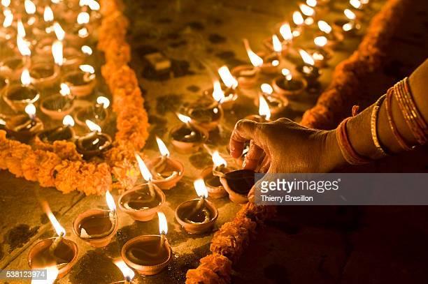 woman lighting candles for shivaratri night - maha shivaratri stock pictures, royalty-free photos & images