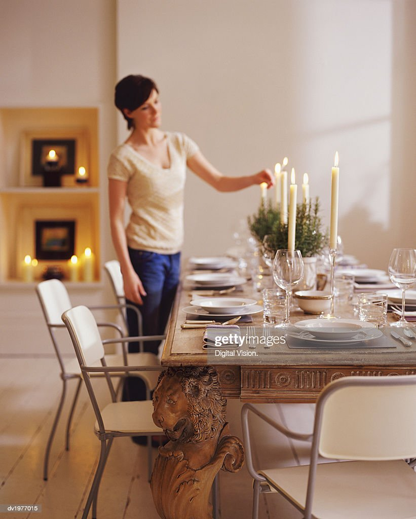 Woman Lighting Candles on a Dining Table in Preparation for a Dinner Party : Stock Photo