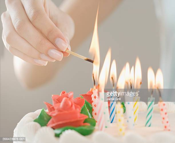 Woman lighting candles on cake, close-up