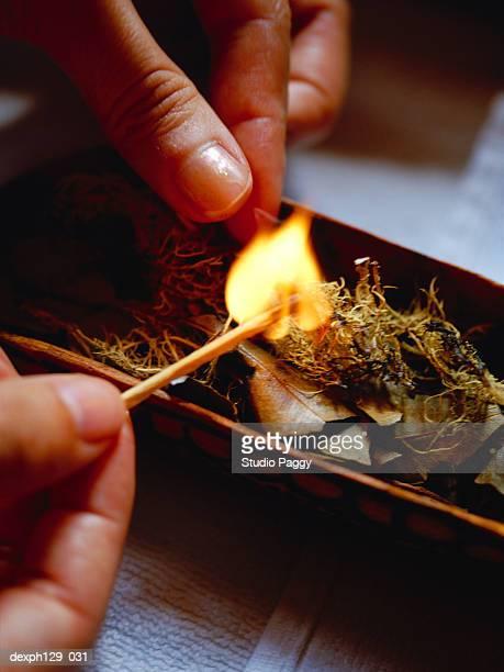 Woman lighting fire on herbs