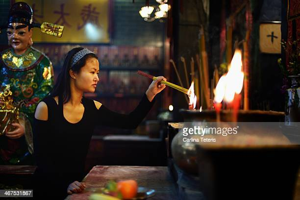 Woman lighting incense in a temple