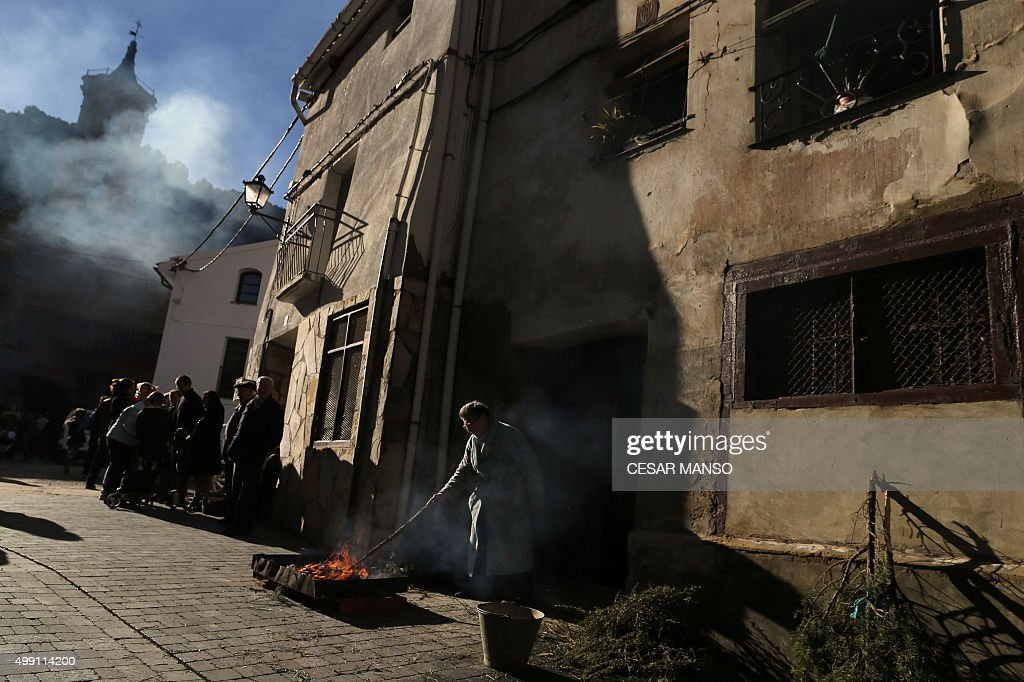 A woman lights a bonfire on November 29, 2015, in the northern Spanish village of Arnedillo prior to celebratring the 'Procession of smoke'. Locals light bonfires with rosemary and junioer to produce smoke that covers Arnedillo streets while the patron saint San Andres is paraded in procession.