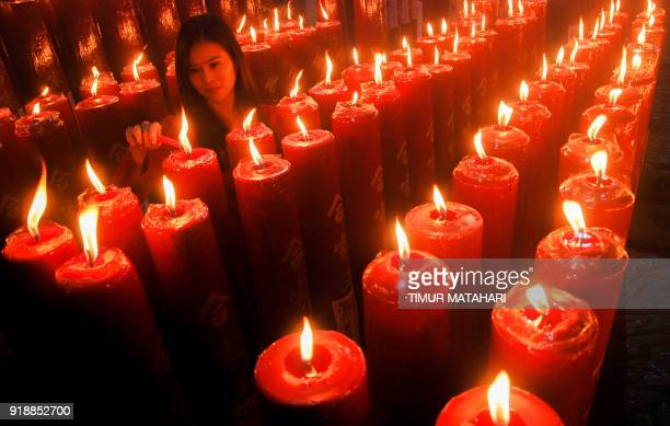 TOPSHOT A woman lights a candal at a Chinese temple to mark the Lunar New Year in Bandung West Java province on February 16 2018 The 2018 Lunar New...