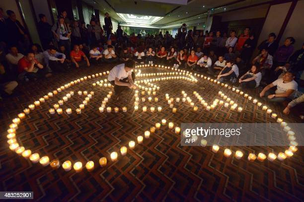 Woman lights a candle as Chinese relatives of passengers on the missing Malaysia Airlines flight MH370 take part in a prayer service at the Metro...