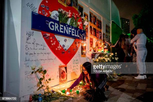 A woman lights a candle as members of the public hold a vigil and commemoration near Grenfell Tower in west London at midnight June 14 2018 to honour...