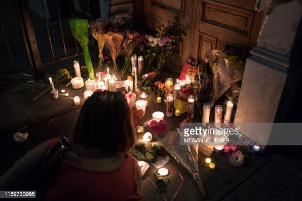 A woman lights a candle at a makeshift memorial as she takes part of a candle lit vigil in honor of those who lost their lives or were wounded in a...