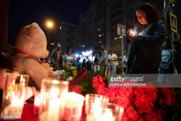 Woman lights a candle at a makeshift memorial for victims of the shooting at School No. 175 in Kazan on May 11, 2021. - At least nine people, most of...
