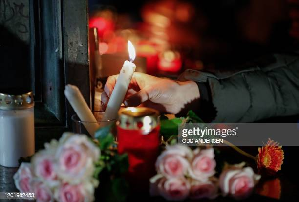 A woman lights a candle at a makeshift memorial in Hanau near Frankfurt am Main western Germany on February 20 after at least nine people were killed...