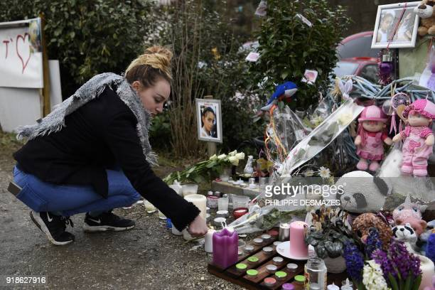 A woman lights a candle at a makeshift memorial in tribute to late eightyearold Maelys de Araujo on February 15 2018 in Le PontdeBeauvoisin near...