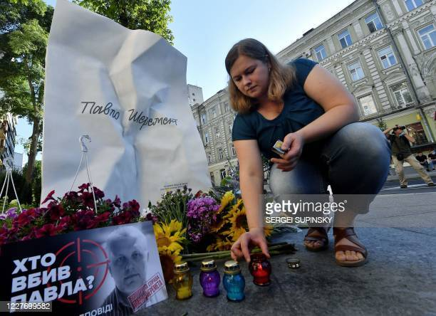 Woman lights a candle at a memorial to journalist Pavel Sheremet on the site where Sheremet's car exploded on the 4th anniversary of his death in...