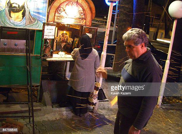 Woman lights a candle at a roadside shrine in Tehran dedicated to Imam Hussein, the grandson of Prophet Mohammad who was martyred at the Battle of...