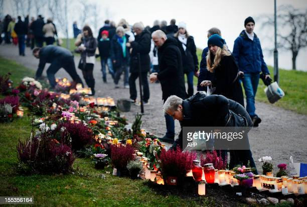 A woman lights a candle at Skogskyrkogarden to celebrate All Saints Day on November 3 2012 in Stockholm Sweden All Saints Day is a public holiday in...