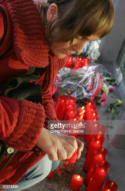 A woman lights a candle at the Atocha railway station 11 March 2005 in memory of the victims of the 11 March 2004 train bombings in Madrid Spain...