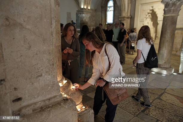 A woman lights a candle at the Cenacle of Mount Zion after Pentecost prayer outside the Old City of Jerusalem on May 24 2015 The Cenacle or Upper...