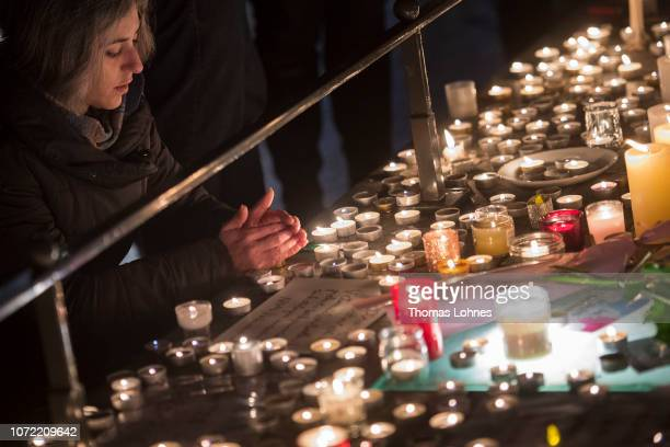 A woman lights a candle at the Christmas market where the day before a man shot 14 people killing at least three on December 12 2018 in Strasbourg...