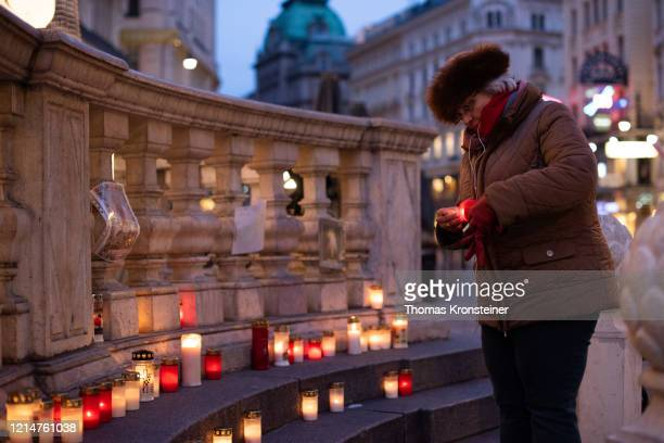 A woman lights a candle at the Plague Column erected after the Great Plague epidemic in 1679 at Graben on March 25 2020 in Vienna Austria The...