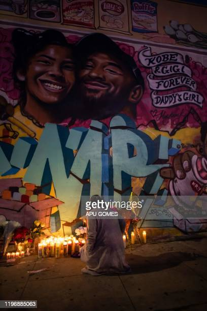 A woman lights a candle below a mural by the artists Muck Rock and Mr79lts showing Kobe Bryant and his daughter Gianna Bryant who were killed with...