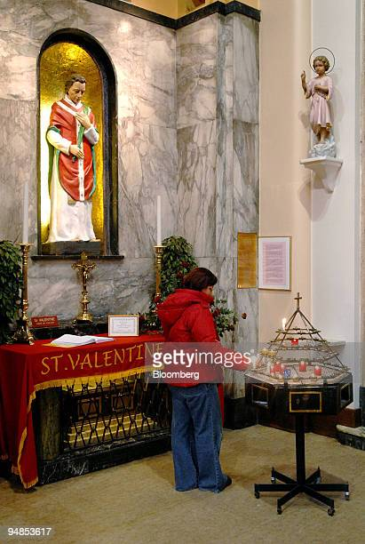 A woman lights a candle beside the remains of St Valentine in Our Lady of Mount Carmel church in Dublin Ireland Monday February 13 2006 Forget Paris...