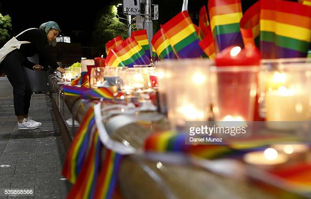 A woman lights a candle during a candlelight vigil for the victims of the Pulse Nightclub shooting in Orlando Florida at Oxford St on June 13 2016 in...