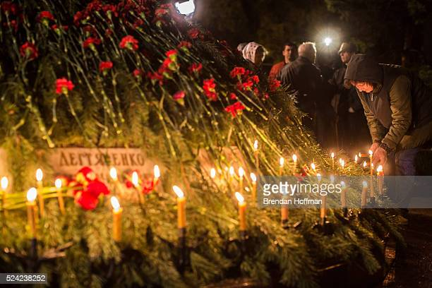 A woman lights a candle during a commemoration of the 30th anniversary of the Chernobyl nuclear accident at St Michael the Archangel Orthodox Church...
