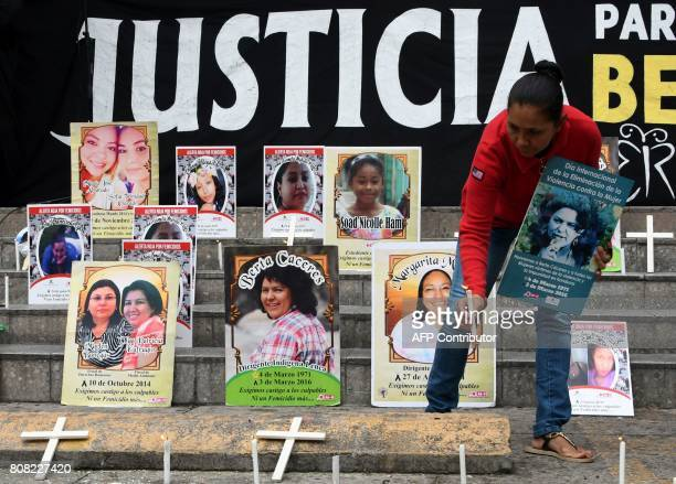 Woman lights a candle during a demonstration to demand justice for the 2016 murder of Honduran environmental activist Berta Caceres and 175 other...