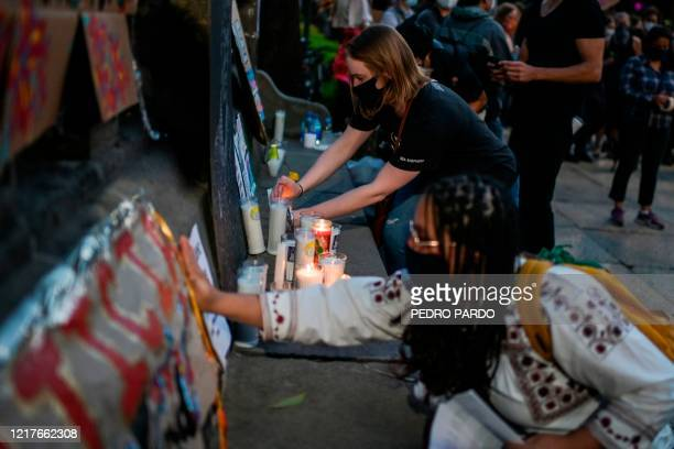 A woman lights a candle during a protest in front of the US embassy in Mexico City on June 4 over the death of George Floyd in police custody in...