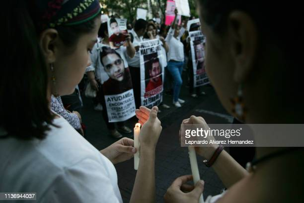 Woman lights a candle during a protest to demand justice a year after the killings of three film students on March 19, 2019 in Guadalajara, Mexico....