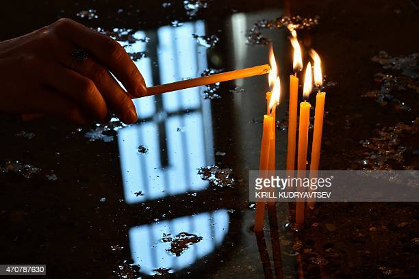 A woman lights a candle during a religious service at the cathedral in Etchmiadzin outside Yerevan on April 23 ahead of the canonization ceremony for...