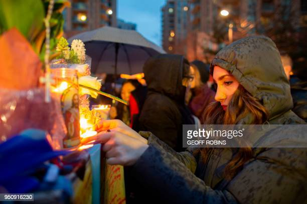 A woman lights a candle during a vigil April 24 2018 in Toronto Canada near the site of the previous day's deadly street van attack A van driver who...