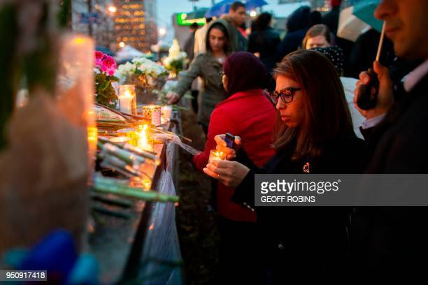 A woman lights a candle during a vigil near the site of the deadly van attack April 24 2018 in Toronto Ontario A van driver who ran over 10 people...
