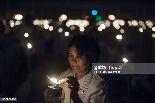 A woman lights a candle during Makha Bucha Day celebrations at Wat Phra Dhammakaya temple near Bangkok on March 1 2018 Makha Bucha Day is held in...