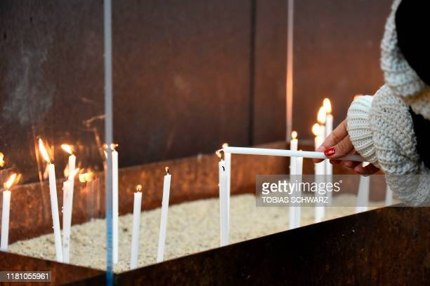 Woman lights a candle during the central commemoration ceremony for the 30th anniversary of the fall of the Berlin Wall, on November 9, 2019 at the...