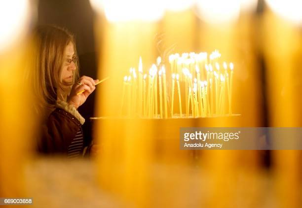 A woman lights a candle during the Easter celebrations at the Saint Jovan Bigorski monastery in Rostusa Macedonia on April 15 2017 The Macedonian...