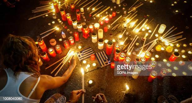 A woman lights a candle during the vigil service in memory of the victims of the deadly fires People gathered outside Hellenic parliament as they...